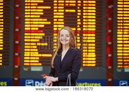 Woman With Hand Luggage In International Airport Terminal, Looking At Information Board