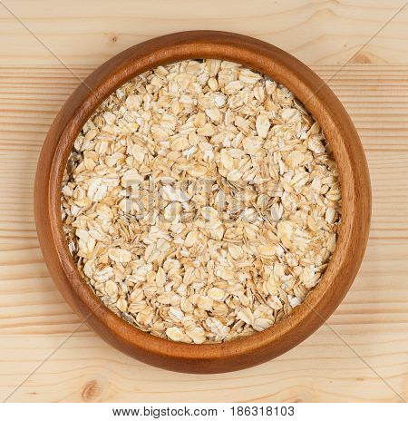 Raw porridge in a bamboo bowl over wooden background