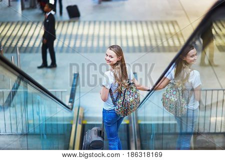 Tourist Girl With Backpack And Carry On Luggage In International Airport, On Escalator