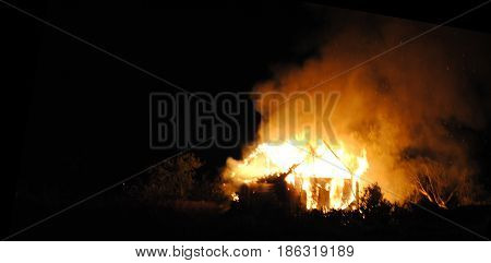 Night fire of a wooden house. Insurance payments abstract