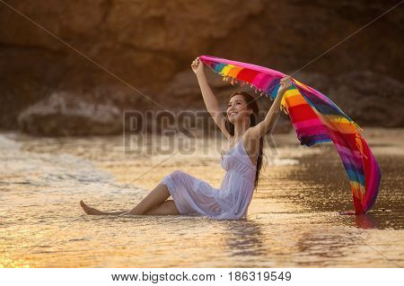 Asian girl swimming on tropical beach by the sea. Enjoy the sea breeze happily near the sunset.