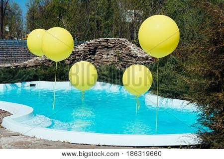 Pool With Big Yellow Balloons Outdoor. Poolside Party. The Balloons On Water. Decorations For Weddin