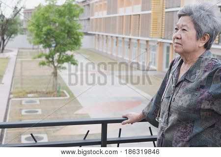 Senior Elder Standing On Balcony Looking At The City View, Elderly Asian Woman Enjoying Nice Weather