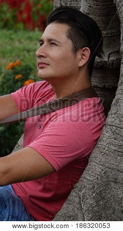 Man Thinking Or Daydreaming Sitting Next to Tree