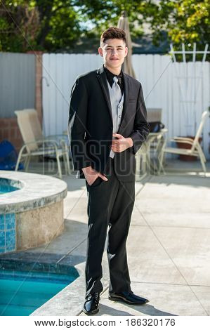 Handsome Mexican teen with hand in pocket of formal black suit.