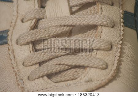 Close up brown shoelace of dirty sneaker.