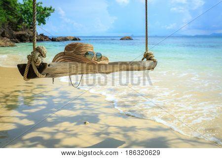 Swing hanging under the tree at mai-ton island Phuket Thailand hat on swing glasses beach