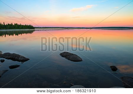 Endless polar day in the Arctic. Night the lake turned into a mirror. Many beautiful combinations of warm orange and cool blue. Beautiful sky reflected in the lake. In the lake a lot of round stones