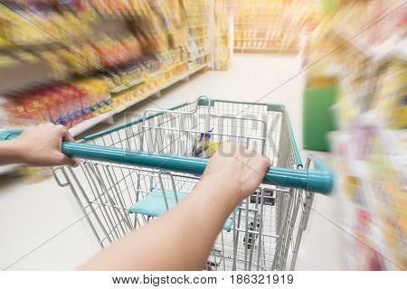 Woman pushing shopping trolley in supermarket with motion blur background