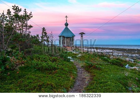 Endless polar day in the Arctic. On the shore of the White sea there is a lonely Christian chapel. Dramatic sky with clouds at night. Breathtaking pink color of a summer night in the Arctic