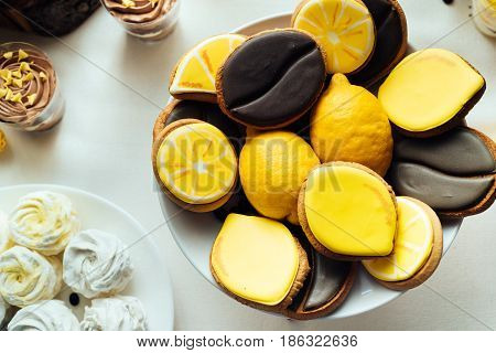 Lemon And Coffee Biscuits On Wedding Candy Bar. Holiday Candy Bar In Yellow And Brown Color