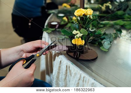 Bunch Of Yellow Roses. Woman's Hands Cutting Brown Ribbon. Florist's Hands Making Flower Composition