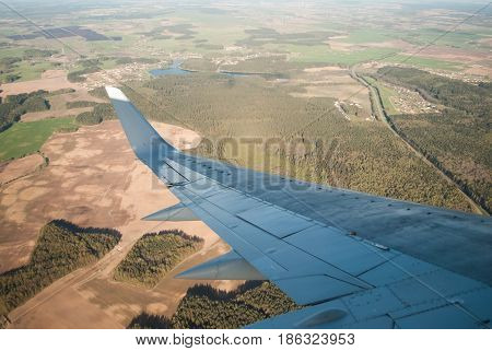 the wing of the plane during the flight over the landscape. to watch during the flight over fields and forest