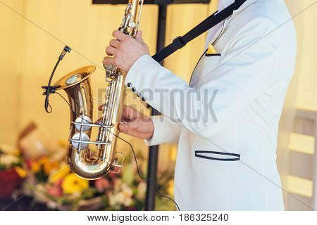 Saxophonist In White Jacket Plays The Saxophone. Saxophonist Jazz Man With Saxophone On Wedding Part