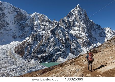 Active Hiker Trekking In Nepal Towards A Hight Mountain Peak And Blue Moraine Lake In Himalaya Lands
