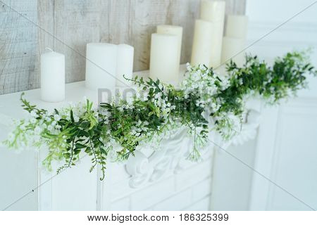 White Decorative Fireplace With Candles On It Near Wooden Wall. Floral Decoration Of White Flowers A