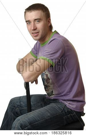 Young Happy Man Is Sitting By Sideways On Chair Black Chair.