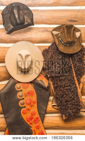 Western hats and chaps hanging on a log cabin wall. Chaps have ornate designs and animal fur.