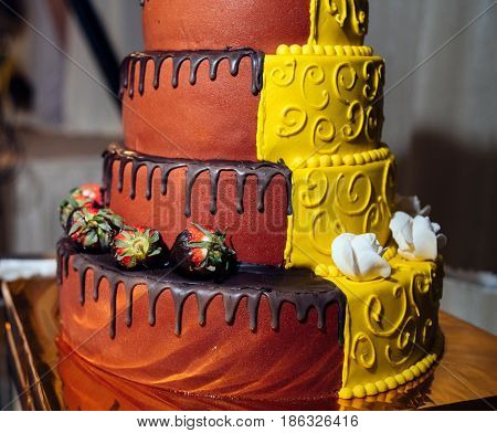 Round Multi Tiered  Yellow And Brown Wedding Cake With Strawberries, Roses And Chocolate Icing