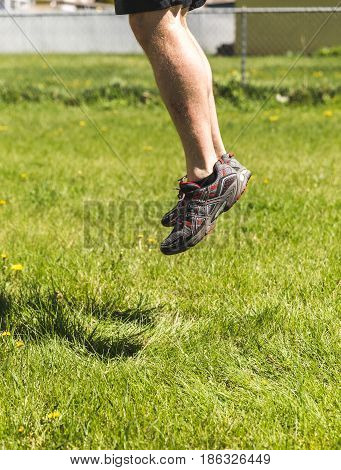 Man's legs and feet jumping in the air over a green grass lawn.
