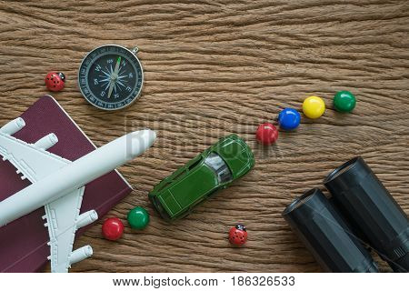 airplane passport compass binoculars and miniature car on wood table as travel planning road trip concept.