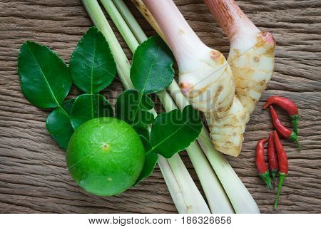 Tom yam ingredient lemon lemongrass galangal and chili on wood table for thai spicy soup.