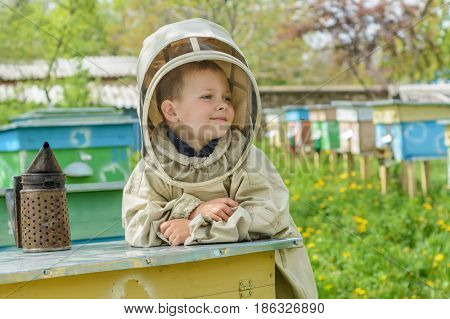 The boy in protective clothing beekeeper works on an apiary. Apiculture
