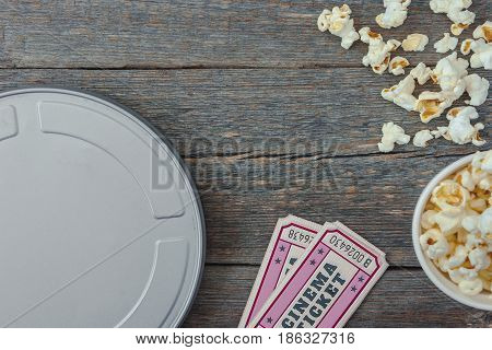 Tin box with movie tickets to the cinema and pack with popcorn stand on a wooden table.