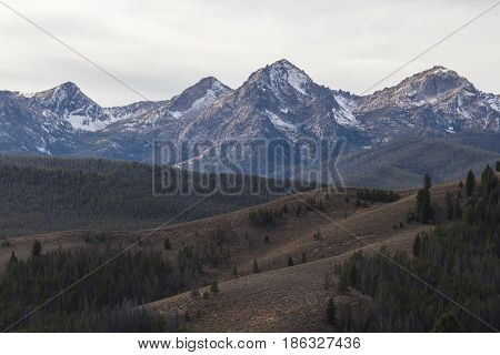 Snowcapped peaks and rolling green hills near Stanley Idaho USA.