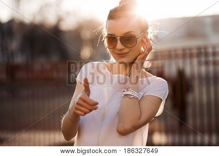 Beautiful smiling woman in sunglasses, white top, listening good music in headphones and gesturing super by big finger. Stylish and fashionable girl relaxing and enjoying life. Street fashion.