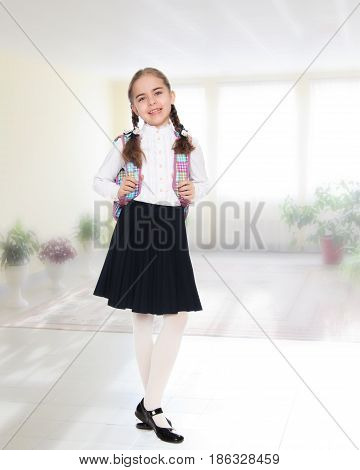Beautiful little blond schoolgirl, with long neatly braided pigtails. In a white blouse and a long dark skirt.She wears a school satchel.In the room with the big bright window in the wall.