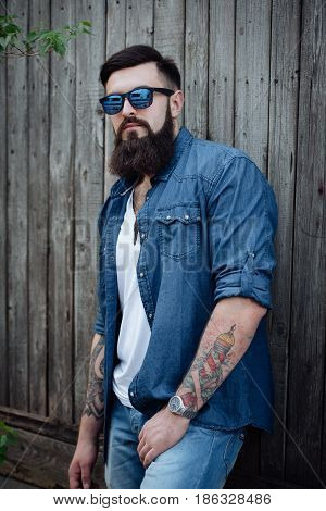 Portrait Of A Serious Brutal Stylish Bearded Man With Tattoo In Jeans Shirt Outdoors. Woodden Backgr