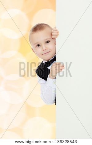 Beautiful little boy in a strict black suit , white shirt and tie.Boy peeping over white banner.Brown festive, Christmas background with white snowflakes, circles.