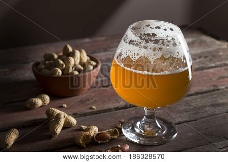 Half-drank glass of cold light unfiltered beer and a bowl of peanuts on a rustic wooden pub table