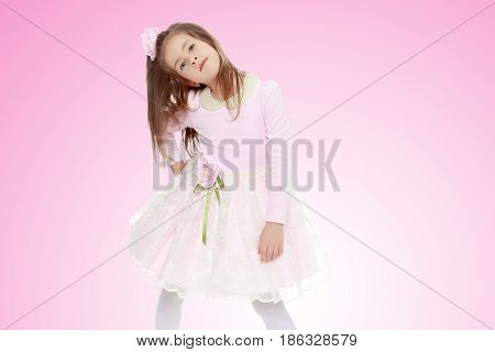 Dressy little girl long blonde hair, beautiful pink dress and a rose in her hair.She put forth a foot.Pale pink gradient background.