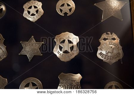Collection of vintage or antique police badges inside a glass case.
