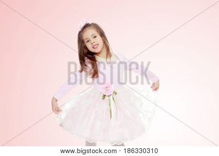 Dressy little girl long blonde hair, beautiful pink dress and a rose in her hair.It stretches over the edges of the dress.Pale pink gradient background.