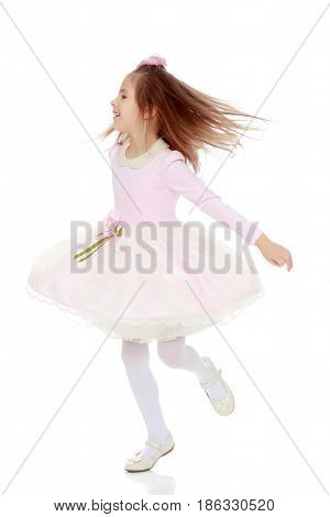 Dressy little girl long blonde hair, beautiful pink dress and a rose in her hair.She whirls around , her dress flying.Isolated on white background.