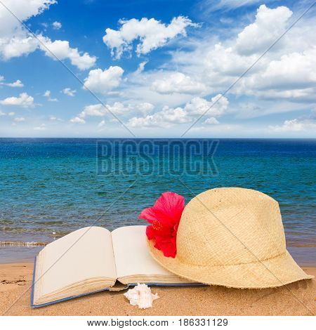 straw hat and book on beach sand by sea side