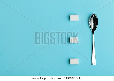 Spoon and sugar cubes on turquoise background, the view from the top with place for your text. Conceptual food photos