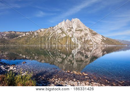 The mirror water of the lake reflects sharp peaks and rocks. Pyramidal mountain in the city of San Carlos de Bariloche. The concept of exotic and extreme tourism