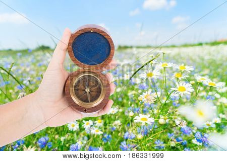 Someones hand holding old vintage compass, summer meadow in background