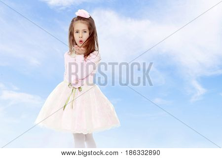 Dressy little girl long blonde hair, beautiful pink dress and a rose in her hair.She sends a kiss.On the background of summer blue sky and fluffy clouds.