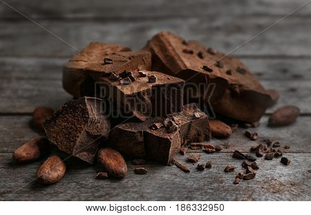 Chunks of chocolate and cocoa beans on wooden background