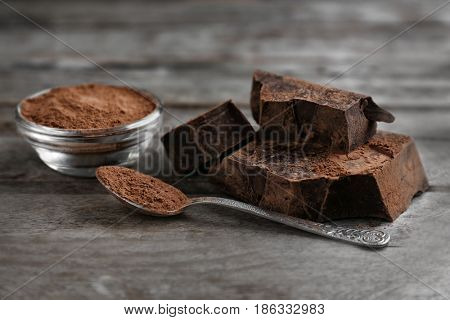 Chunks of chocolate and cocoa powder on wooden background