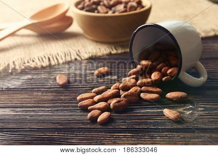 Cup with aromatic cocoa beans on wooden table