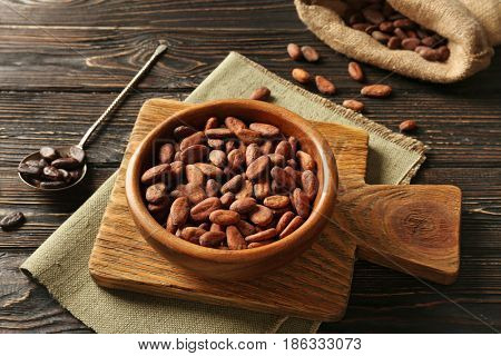 Bowl with aromatic cocoa beans on wooden background