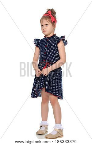 Little girl in blue polka dot dress with a red bow on his head.She shyly pulls hands to the edge of the dress.Isolated on white background.