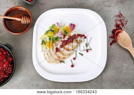 Portion of chicken and cranberry sauce on table