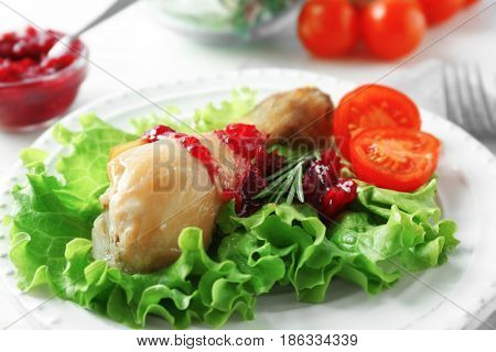 Portion of chicken and cranberry sauce on plate